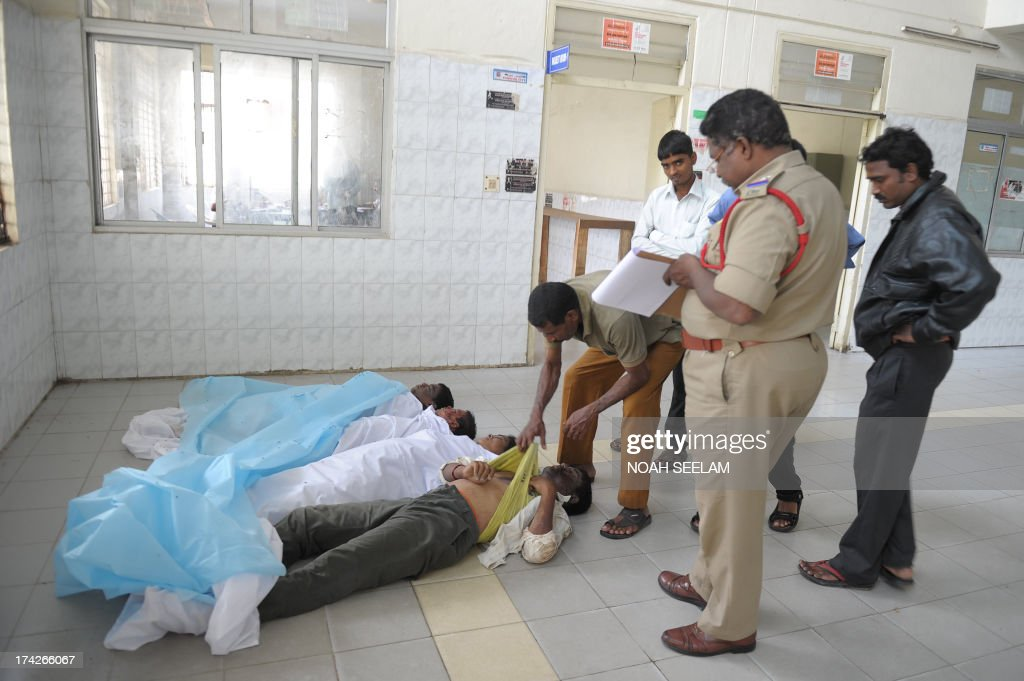 Indian policemen take down details as they check the bodies of men killed in a wall collapse, at the mortuary at Gandhi Hospital in Hyderabad on July 23, 2013. Six people were killed in their sleep in southern India when a mud wall collapsed on their makeshift tenements, rescue officials said. AFP PHOTO / Noah SEELAM