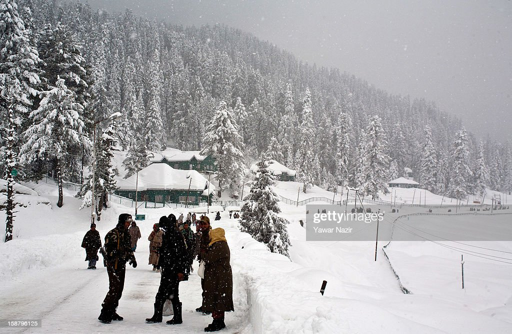Indian policemen take pictures during a snowfall on December 29, 2012 in Gulmarg, 54 km (35 miles) to the west of Srinagar, the summer capital of Indian-administered Kashmir, India. With the second round of heavy snowfall in Kashmir valley, skiers from around the globe have descended on the ski resort of Gulmarg, known for long-run skiing, snow-boarding, heli-skiing and steep mountains. Gulmarg is located less than six miles from the ceasefire line or Line of Control (LoC) that divides Kashmir between India and Pakistan. As a sense of normalcy has started to return to this strife-torn region, various foreign governments, including the United Kingdom, have lifted the travel advisory to its citizens traveling to Kashmir, raising the hopes of the local tourism industry, officials said.