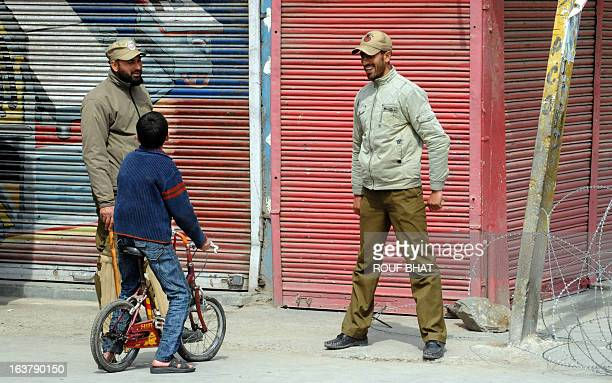 Indian policemen talk to a Kashmiri child during the third day of a curfew imposed on the Kashmiri summer capital in Srinagar on March 16 2013...