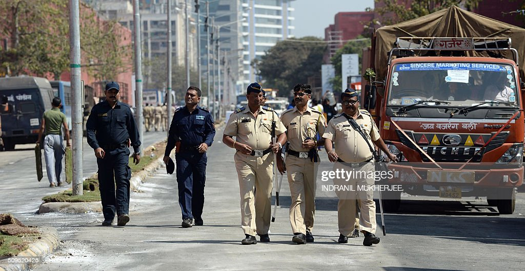 Indian policemen walk at the venue of the 'Make in India' showcase week in Mumbai on February 11, 2016. Over 190 companies, including national conglomerates and multinational corporations, 5,000 delegates from 60 countries, and leading industrialists including Ratan Tata and Mukesh Ambani will be participating in the maiden 'Make in India' showcase to be held in Mumbai from February 13-18. AFP PHOTO/ INDRANIL MUKHERJEE / AFP / INDRANIL MUKHERJEE
