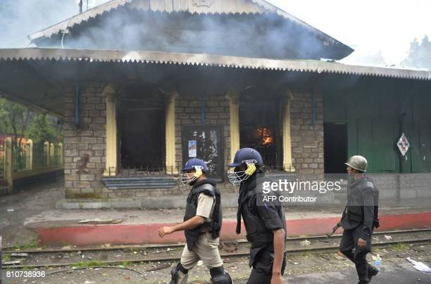 Indian policemen walk pass a train station set alight during clashes with Gorkhaland supporters during an indefinite strike called Gorkha Janamukti...