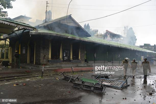Indian policemen walk pass a train station set alight during clashes with Gorkhaland supporters during an indefinite strike called by Gorkha...