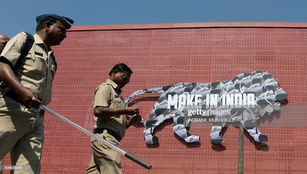 Indian policemen walk past a logo at the venue for the 'Make in India' showcase week in Mumbai on February 11, 2016. Over 190 companies, including national conglomerates and multinational corporations, 5,000 delegates from 60 countries, and leading industrialists including Ratan Tata and Mukesh Ambani will be participating in the maiden 'Make in India' showcase to be held in Mumbai from February 13-18. AFP PHOTO/ INDRANIL MUKHERJEE / AFP / INDRANIL MUKHERJEE