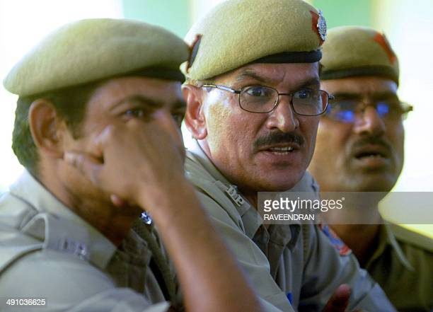 Indian policemen watch election results on a television at a counting centre in New Delhi on May 16 2014 Hindu nationalist Narendra Modi looked set...