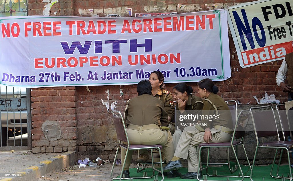 Indian policewomen sit in front banners during a protest against the proposed India-European Union Free Trade Agreement in New Delhi on February 27, 2013. Indian labour union activists demonstrated against the government's decision to allow Foreign Direct investment (FDI).