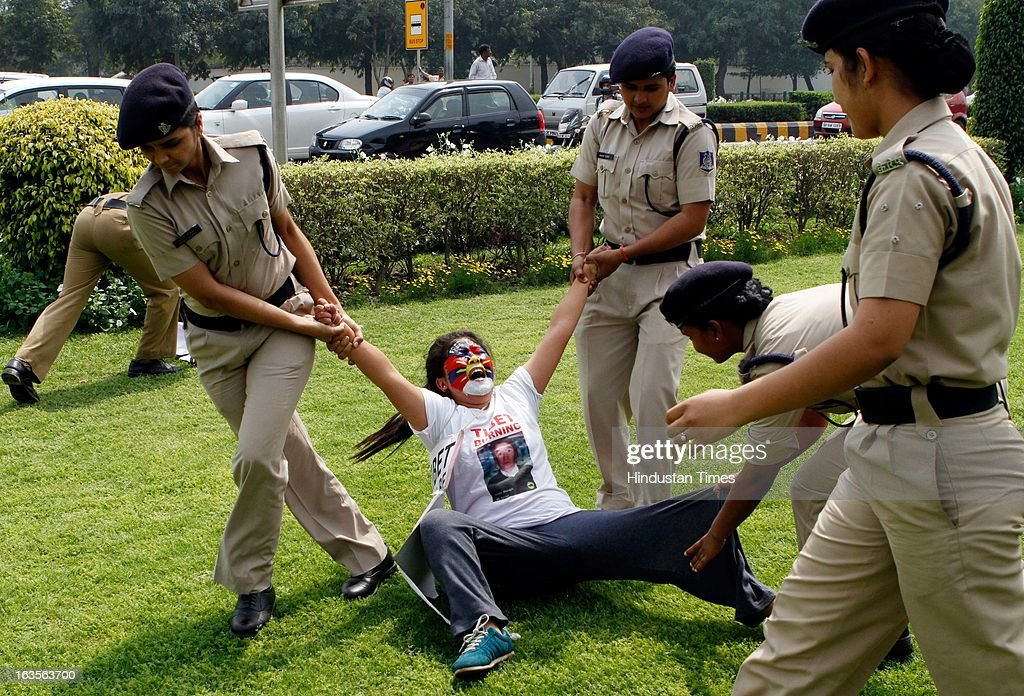 Indian policewomen try to break a human chain formed by exiled Tibetan women during a protest to mark the anniversary of a failed 1959 uprising against Chinese rule outside the Chinese Embassy on March 12, 2013 in New Delhi, India.