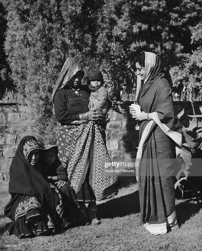 Indian politician Indira Gandhi daughter of Indian Prime Minister Jawaharlal Nehru with two peasant women and their children in the garden of her...