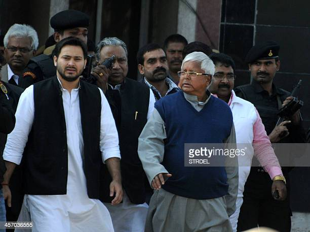 Indian politician Lalu Prasad Yadav walks with his son Tejaswi and security personnel as he leaves Birsa Munda Central Jail in Ranchi on December 16...