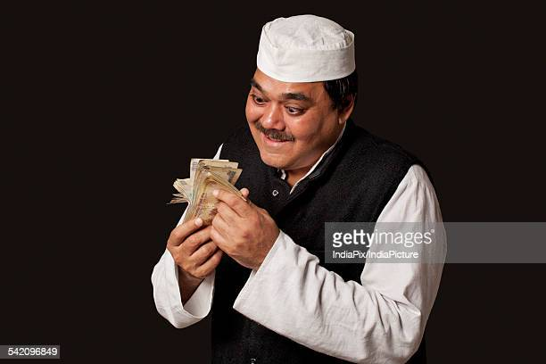 Indian politician taking bribes over black background