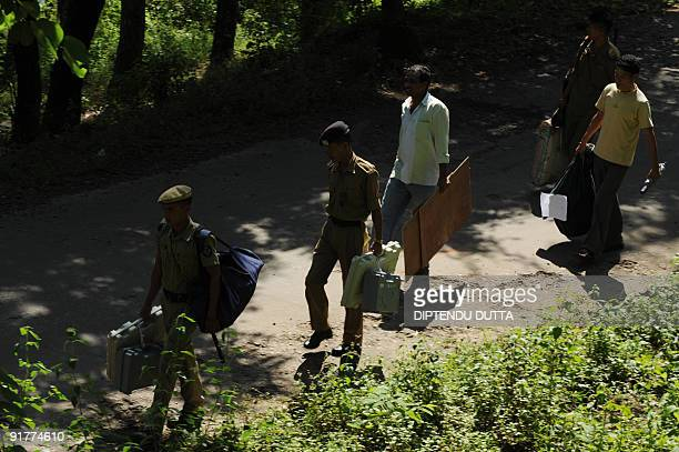 Indian polling officials and security officers head to a polling booth from a temporary election distribution cell in Itanagar capital of...