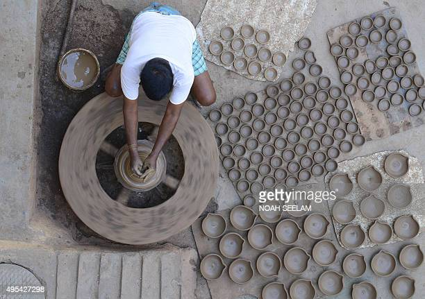 Indian potter Chelimila Veera Swamy makes earthen pots or 'diyas' ahead of the forthcoming Diwali festival on the outskirts of Hyderabad on November...