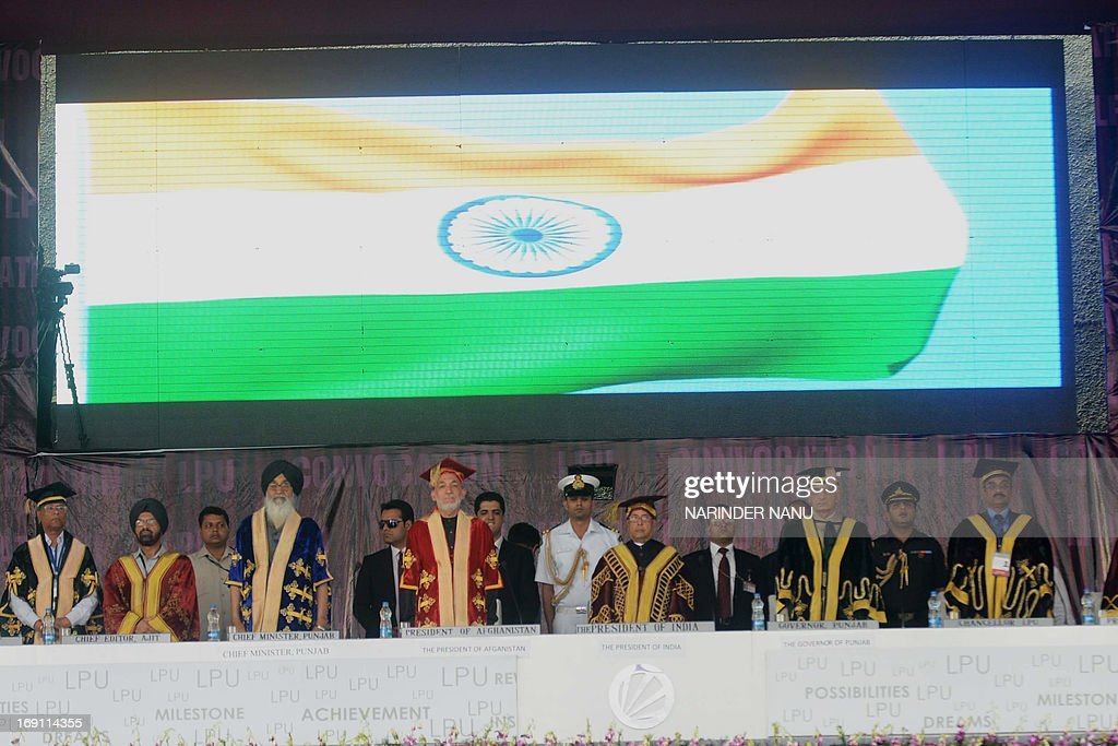Indian President Pranab Mukherjee (C), Afghanistan President Hamid Karzai (6L), Punjab Governor Shivraj Patil (3R), and Chief Minister Parkash Singh Badal (4L)stand for the Indian national anthem during 3rd convocation at Lovely Professional University (LPU) on the outskirts of Jalandhar on May 20,2013. Afghan President Hamid Karzai arrived in India on Monday on a two-day visit during which he is set to seek greater military aid from the government in New Delhi, officials said. The Afghan leader landed in the northern Indian city of Chandigarh for a private function and will reach the national capital later Monday.