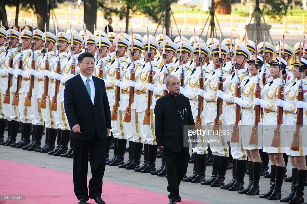 Indian President Pranab Mukherjee (R) and China's President Xi Jinping (L) walk past the honor guard during an official welcome ceremony prior to their meeting in Beijing, China on May 26, 2016.