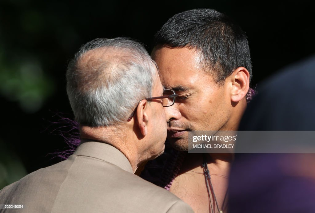 Indian President Pranab Mukherjee (C) is greeted with a Hongi, a traditional Maori greeting, during a welcoming ceremony at Government House in Auckland on April 30, 2016. Mukherjee is in New Zealand for a three-day official visit. / AFP / MICHAEL