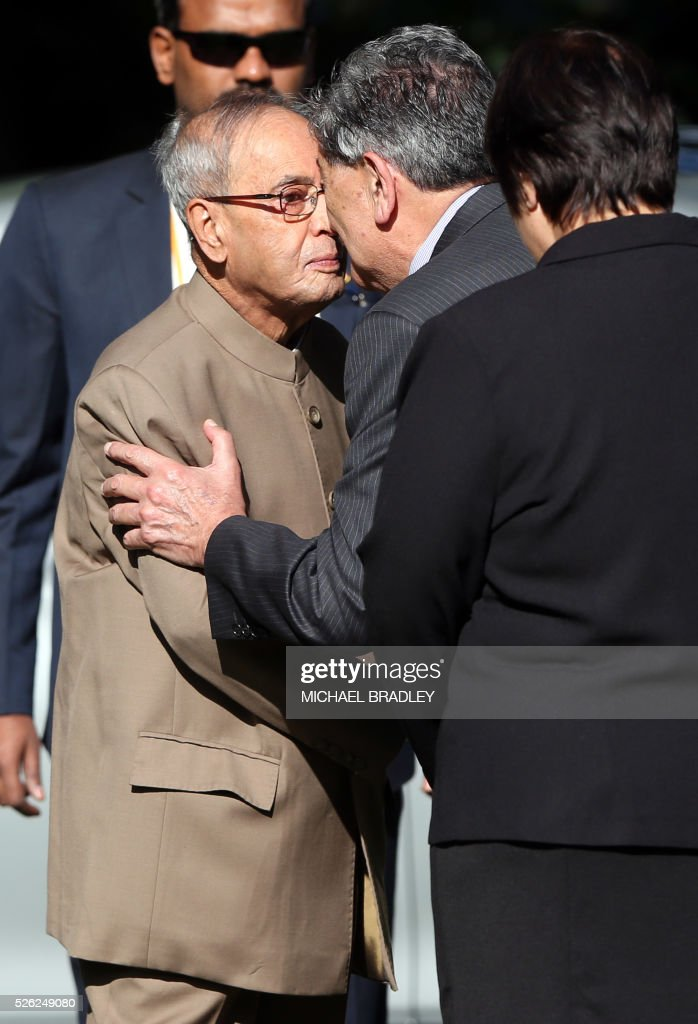 Indian President Pranab Mukherjee (C) is greeted with a Hongi - a traditional Maori greeting - from New Zealand Governor-General Lewis Moeau (R) prior to a welcoming ceremony at Government House in Auckland on April 30, 2016. Mukherjee is in New Zealand for a three-day official visit. / AFP / MICHAEL