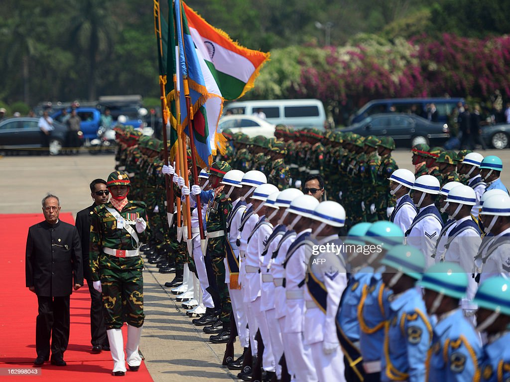 Indian President Pranab Mukherjee (L) walks with officials as he inspects a guard of honour after arriving at Hazrat Shahjalal International Airport in Dhaka on March 3, 2013, at the start of a state visit. Mukherjee is on a three-day state visit to Bangladesh until March 5. AFP PHOTO/Munir uz ZAMAN
