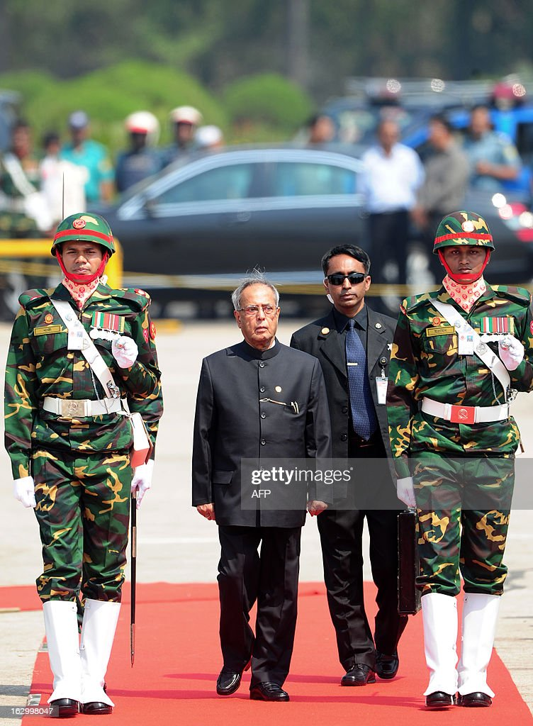 Indian President Pranab Mukherjee (C) walks with officials as he inspects a guard of honour after arriving at Hazrat Shahjalal International Airport in Dhaka on March 3, 2013, at the start of a state visit. Mukherjee is on a three-day state visit to Bangladesh until March 5. AFP PHOTO/Munir uz ZAMAN