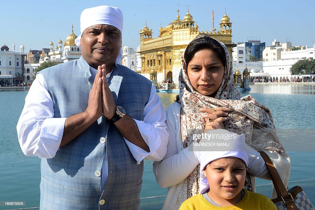 Indian President Pranab Mukherjee's son, Indrajit Mukherjee (L), his wife Sugandhi (R), and son poses for a photo during a visit to the Golden Temple in Amritsar on February 7, 2013. Mukherjee along with his family members visited the city to attend a marriage function and also pay their respects at Sikh Shrine. AFP PHOTO/NARINDER NANU