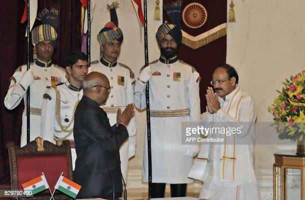 Indian President Ram Nath Kovind greets Venkaiah Naidu after administering the oath of vice president to him during a swearing in ceremony at the...