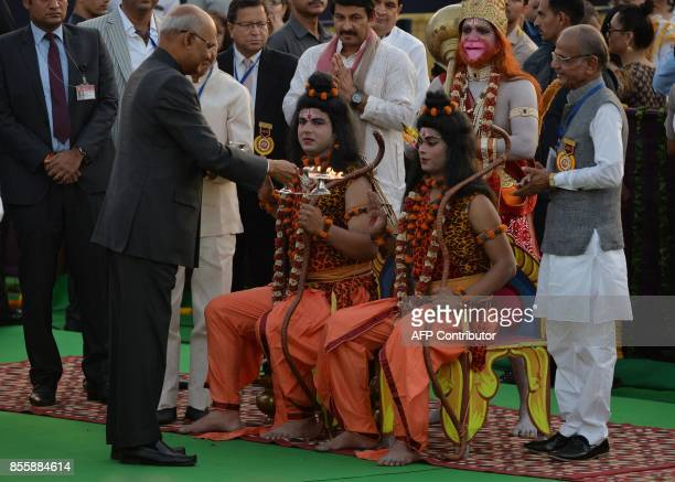 Indian President Ram Nath Kovind performs a religious ritual with performers dressed as Hindu deities Rama and Lakshman ahead of the burning of the...