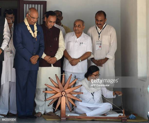 Indian President Ramnath Kovind Gujarat Chief Minister Vijaybhai Rupani watch as a volunteer spins yarn from cotton on a spinning wheel during a...