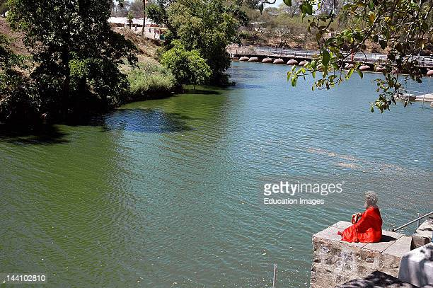 Indian Priest Sadhu Meditating On Calm River Bank