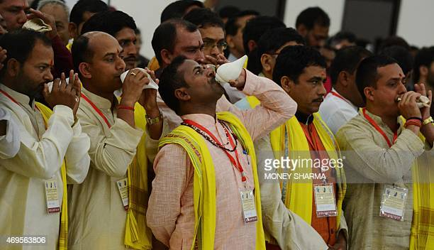 Indian priests blow conch shells traditionally known as a Shankh at the start of the 'Untouchability No More' event in New Delhi on April 13 2015...