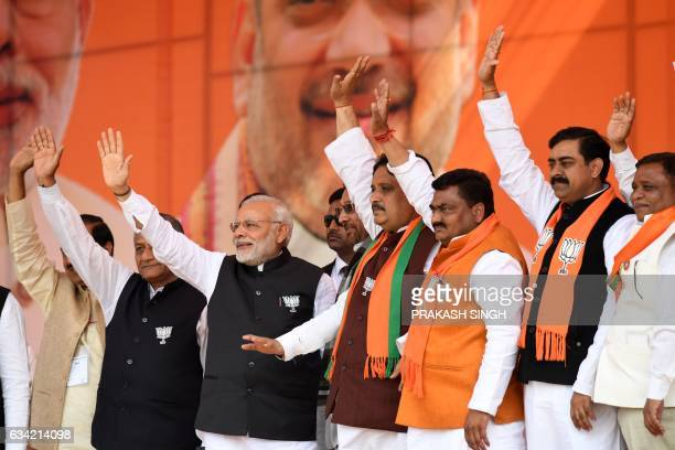 Indian Prime Minister and Bharatiya Janata Party Leader Narendra Modi waves as he stands with party officials during a state assembly election rally...