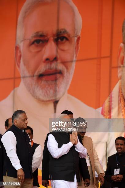 Indian Prime Minister and Bharatiya Janata Party Leader Narendra Modi gestures as he walks alongside former army General VK Singh at a state assembly...