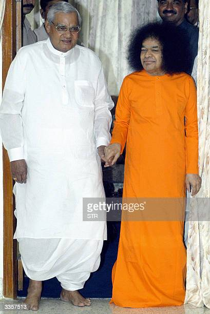 Indian Prime Minister Atal Behari Vajpayee walks out with Hindu holy man Satya Sai Baba after their meeting in Bangalore 14 April 2004 Vajpayee who...