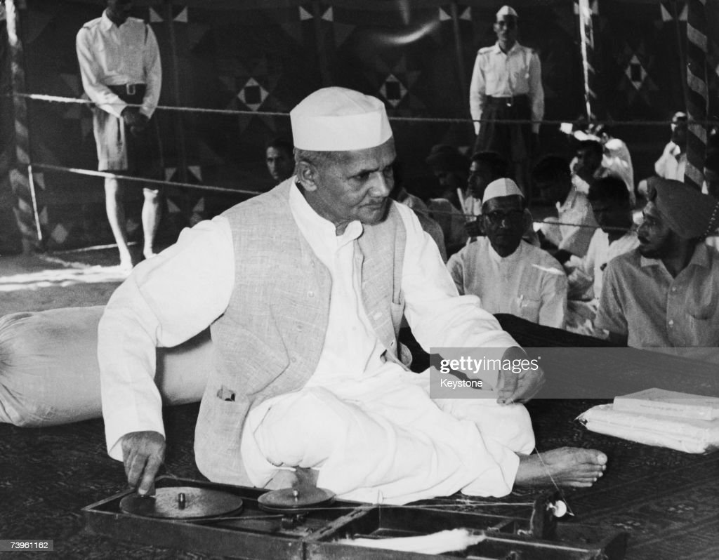 Indian Prime Minister Lal Bahadur Shastri (1904 - 1966) celebrates his own and Mahatma Gandhi's birthday at Gandhi's samadhi, or cremation spot, in Delhi, 2nd October 1965. He is using a charkha or spinning wheel, popularised as a symbol of Indian independence by Gandhi.