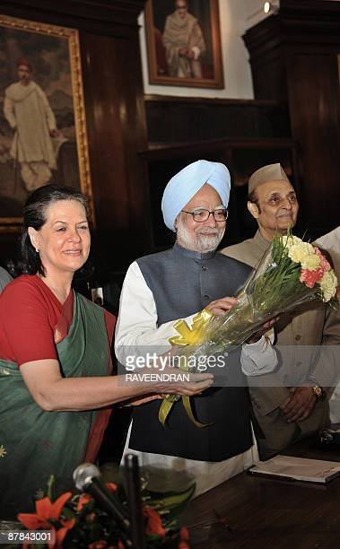 Indian Prime Minister Manmohan Singh and Congress Party President Sonia Gandhi pose with a bouquet of flowers at the meeting of The Congress...