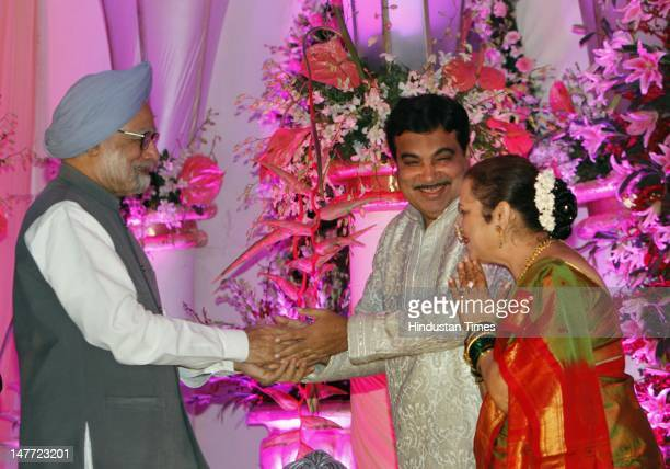 Indian Prime Minister Manmohan Singh greets BJP presdent Nitin Gadkari and his wife Kanchan Gadkari during a wedding reception of Gadkar's son Sarang...