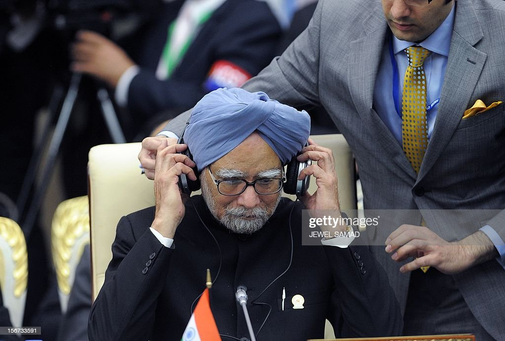 Indian Prime Minister Manmohan Singh is assisted to adjust a headphone during an East Asian Summit Plenary Session at the Peace Palace in Phnom Penh on November 20, 2012. Cambodian is hosing the 21st Association of Southeast Asian Nations (ASEAN) Summit and Related Summits. AFP PHOTO/Jewel Samad