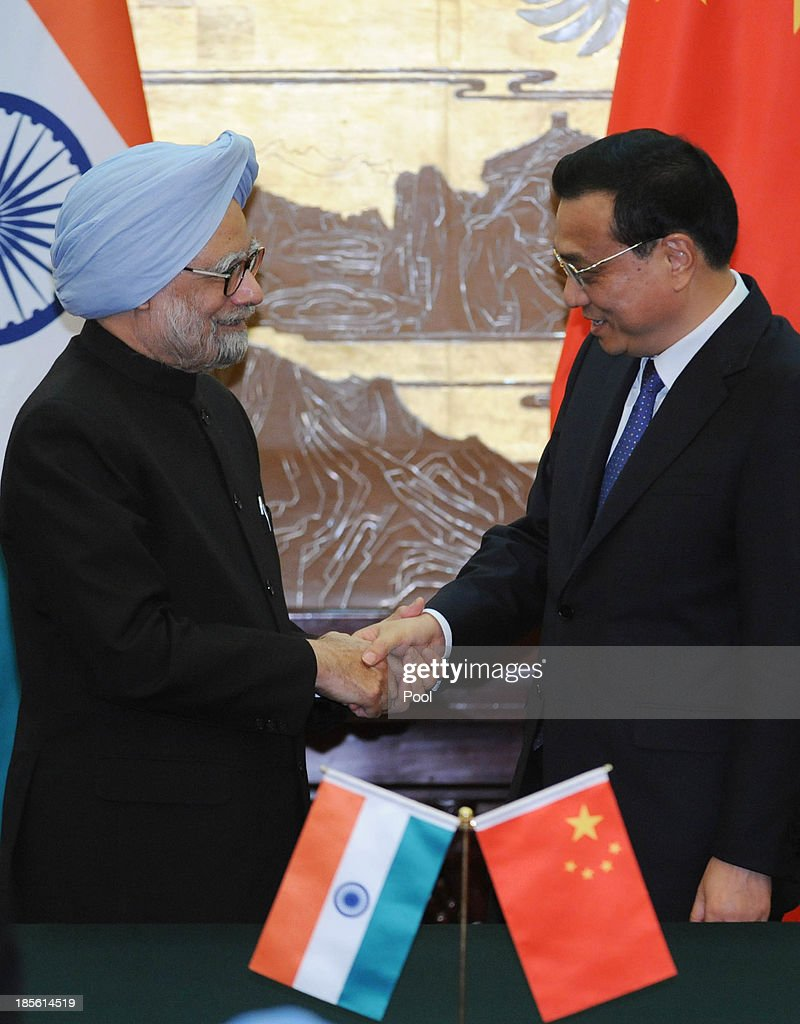 Indian Prime Minister <a gi-track='captionPersonalityLinkClicked' href=/galleries/search?phrase=Manmohan+Singh&family=editorial&specificpeople=227120 ng-click='$event.stopPropagation()'>Manmohan Singh</a> shakes hands with Chinese Premier <a gi-track='captionPersonalityLinkClicked' href=/galleries/search?phrase=Li+Keqiang&family=editorial&specificpeople=2481781 ng-click='$event.stopPropagation()'>Li Keqiang</a> after a joint news conference at the Great Hall of the People on October 23, 2013 in Beijing, China. Singh is on a three-day visit to China to discuss various issues, including an agreement to sign a deal on border cooperation between the two countries.