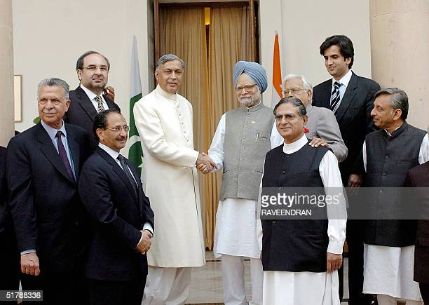 Indian Prime Minister Manmohan Singh shakes hands with Pakistani Prime Minister Shaukat Aziz as Pakistani and Indian Ministers look on after a...