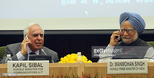 Indian Prime Minister Manmohan Singh speaks over mobile phone with Indian Minister for Communication and Information Technology Kapil Sibal while...