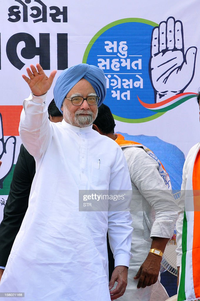 Indian Prime Minister, Manmohan Singh waves as arrives on stage to address a political rally in support of Congress Party at Vansda town, some 350 kms from Ahmedabad on December 9, 2012. Gujarat state goes to polls in two phases, December 13 and 17, 2012. AFP PHOTO
