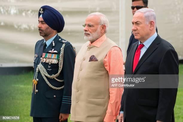 Indian Prime Minister Narendra Modi and Israeli Prime Minister Benjamin Netanyahu stand alongside an Indian army officer at the Indian Army Cemetery...