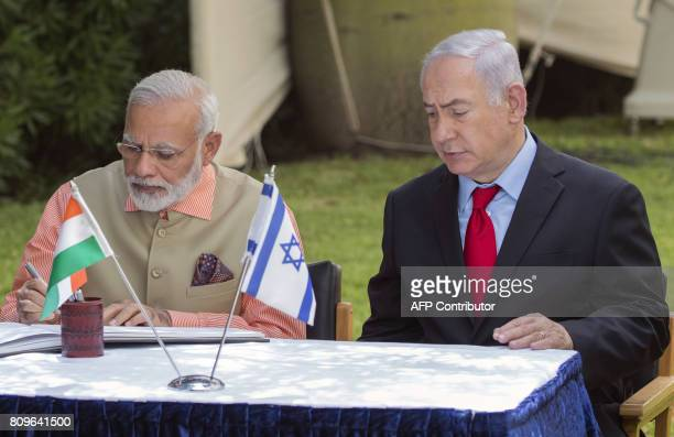 Indian Prime Minister Narendra Modi and Israeli Prime Minister Benjamin Netanyahu sign the guest book at the Indian Army Cemetery of the World War I...