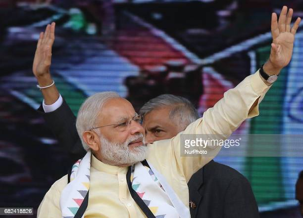 Indian Prime Minister Narendra Modi and Sri Lankan Prime Minister Ranil Wickremesinghe wave to Sri Lankan tea plantation workers of Indian origin...