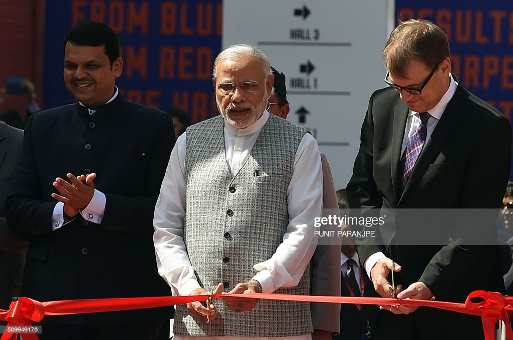 Indian Prime Minister Narendra Modi (C) cuts a ribbon as Finnish Prime Minister Juha Sipila (R) and Maharashtra Chief Minister Devendra Fadanvis look on during the opening of the 'Make in India Week' in Mumbai on February 13, 2016. Over 190 companies, and 5,000 delegates from 60 countries, are taking part in the first 'Make in India Week' to be held in Mumbai from February 13-18. AFP PHOTO/ PUNIT PARANJPE / AFP / PUNIT PARANJPE