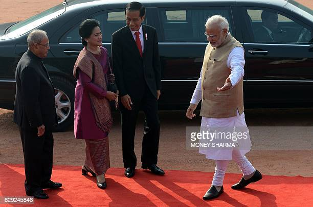Indian Prime Minister Narendra Modi gestures to Indonesian President Joko Widodo and his wife HJ Iriana as Indian President Pranab Mukherjee looks on...