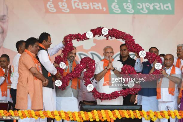 Indian Prime Minister Narendra Modi gestures while being garlanded in rose petals in the formation of a map of Gujarat State during Gujarat Gaurav...
