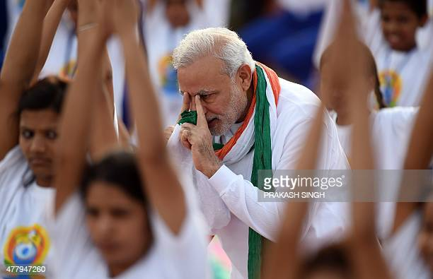 Indian Prime Minister Narendra Modi gives instructions as Indian yoga practitioners take part in a mass yoga session to mark the International Yoga...