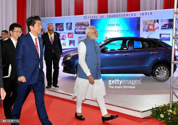 Indian Prime Minister Narendra Modi inspects Suzuki Motor booth with Japanese Prime Minister Shinzo Abe on September 14 2017 in Gandhinagar India Abe...