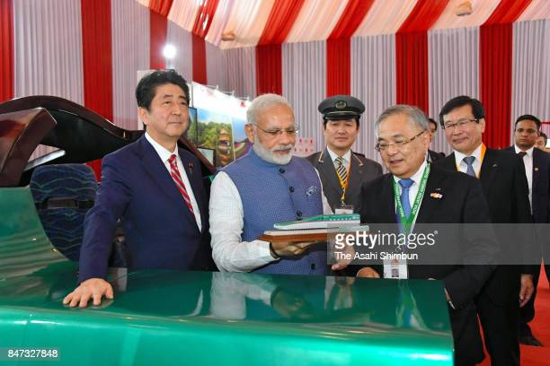 Indian Prime Minister Narendra Modi is presented a model of a high speed train by Japanese Prime Minister Shinzo Abe and JR East President Tetsuro...