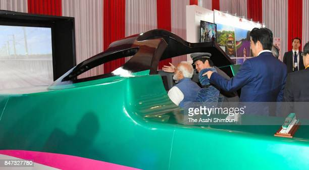 Indian Prime Minister Narendra Modi operates a high speed train simulator in the driving seat while Japanese Prime Minister Shinzo Abe watches during...