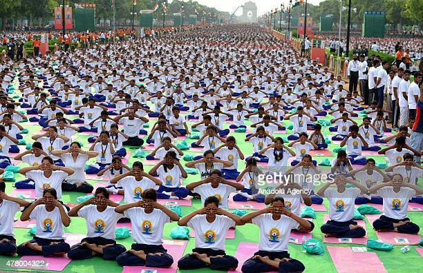Indian Prime Minister Narendra Modi performs yoga along with others at Rajpath during mass yoga session to mark the International Day of Yoga on June...