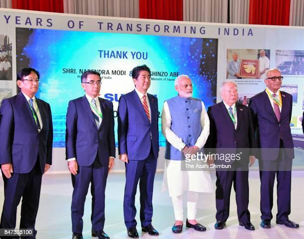 Indian Prime Minister Narendra Modi poses with Japanese Prime Minister Shinzo Abe and Suzuki Motor Chairman Osamu Suzuki at the company booth on...